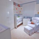 Móveis em MDF branco brilhante sendo o berço, armário com 2 portas e cômoda multifuncional.