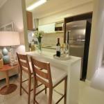 Cozinha americana branca com bancada para banquetas